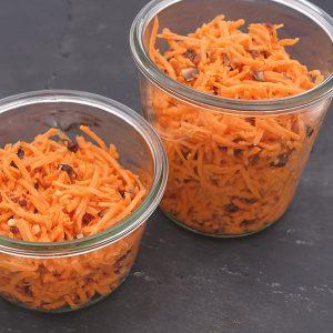 Bocaux de carottes râpées soupoudrées d'amandes sur une ardoise